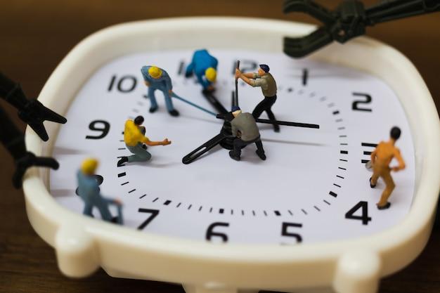 Pessoas em miniatura: a equipe está trabalhando em um despertador