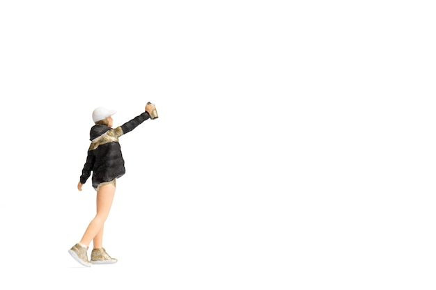Pessoas em miniatura adolescente pulverizando tinta de uma lata em fundo branco e espaço para texto
