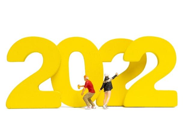 Pessoas em miniatura adolescente pulverizando tinta número 2022 em fundo branco, conceito de feliz ano novo
