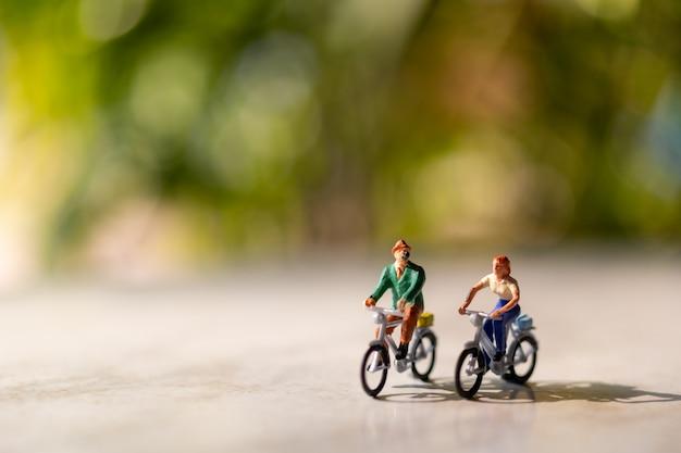 Pessoas em miniatura andam de bicicleta ao ar livre com fundo verde bokeh