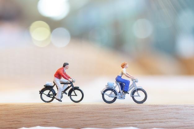 Pessoas em miniatura, andar de bicicleta na ponte de madeira