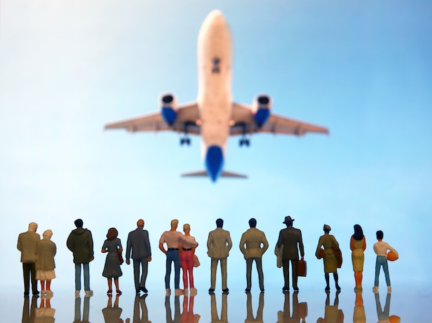 Pessoas em miniatura assistindo um avião voando sobre eles