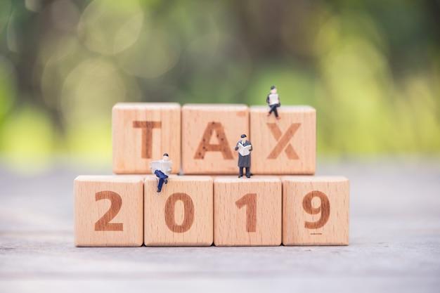 Pessoas em miniatura, bloco de palavra de empresários tax 2019