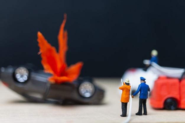 Pessoas em miniatura: bombeiros em um acidente de carro