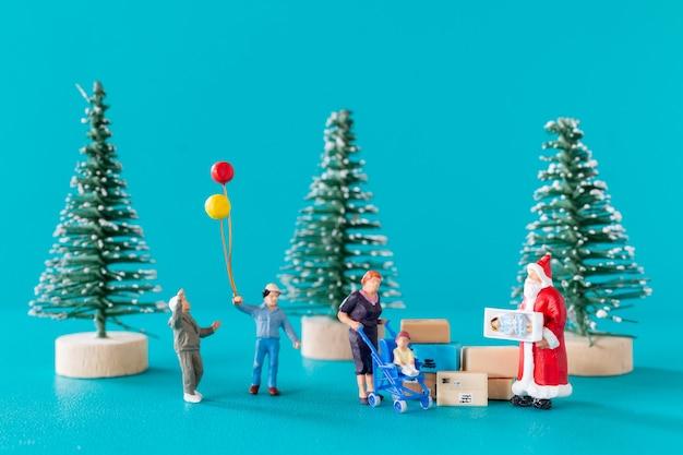 Pessoas em miniatura, caixa de presente de entrega de papai noel para crianças, conceito de natal e feliz ano novo.