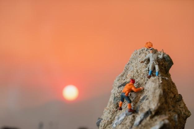 Pessoas em miniatura: caminhantes subindo na rocha. conceito de esporte e lazer.