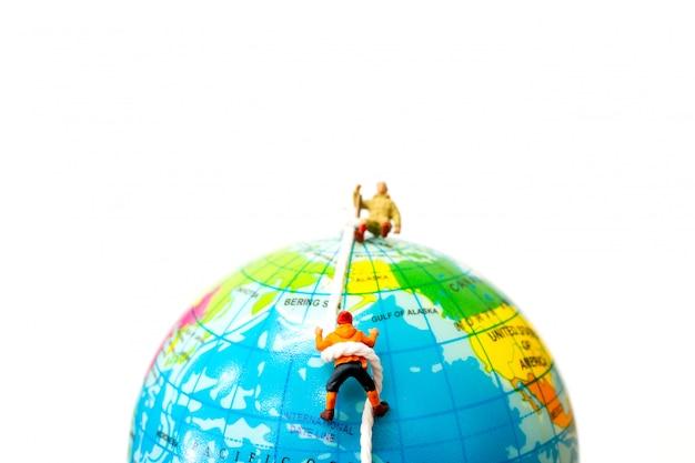 Pessoas em miniatura: caminhantes subindo no globo