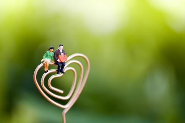 Pessoas em miniatura casal amante sentado no coração.