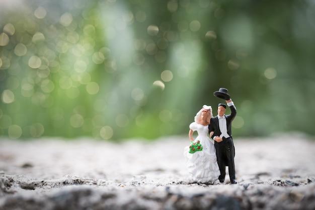Pessoas em miniatura: casal de noivos em pé ao ar livre
