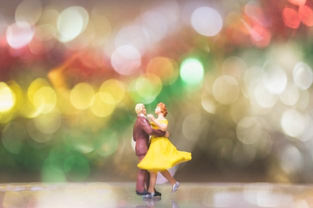Pessoas em miniatura: casal romântico dançando com fundo de bokeh