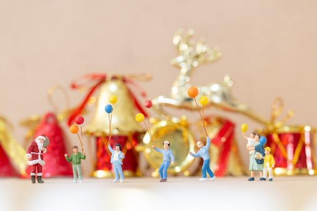 Pessoas em miniatura celebrando o natal