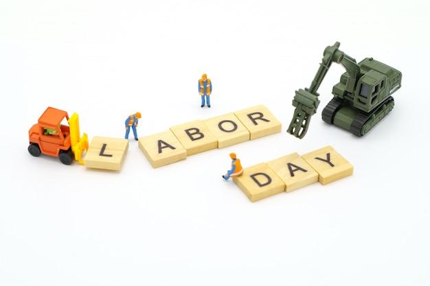 Pessoas em miniatura com a palavra madeira dia do trabalho