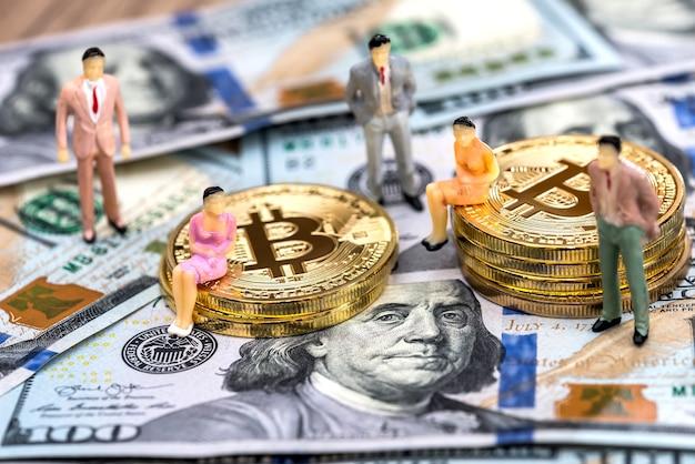 Pessoas em miniatura com bitcoins e dólares