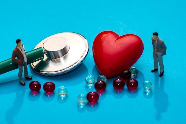 Pessoas em miniatura com estetoscópio, pílulas e forma de coração isolada em azul