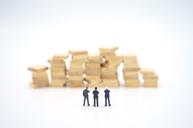 Pessoas em miniatura com pilha de notas de pé