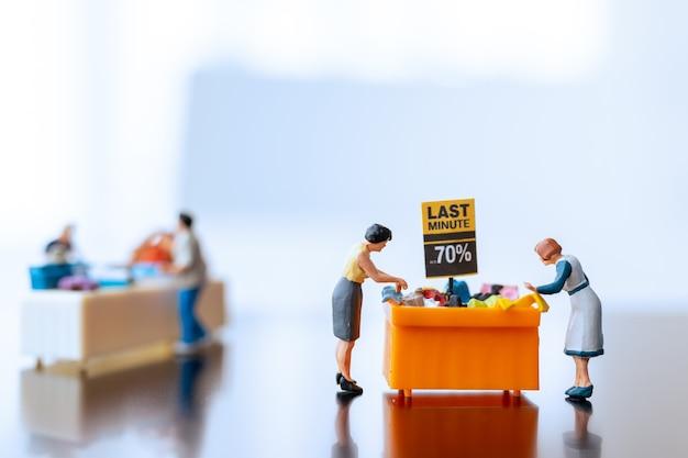 Pessoas em miniatura, compradores com bandeja de descontos para comprar itens com desconto