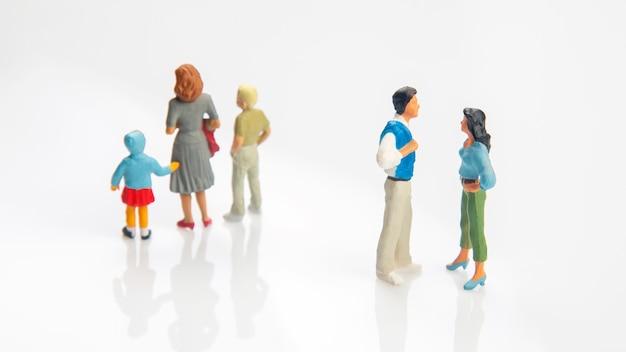 Pessoas em miniatura. conceito de pessoas da família nos relacionamentos em um fundo branco. o problema da fidelidade no casamento. criar os filhos em relacionamentos problemáticos na família