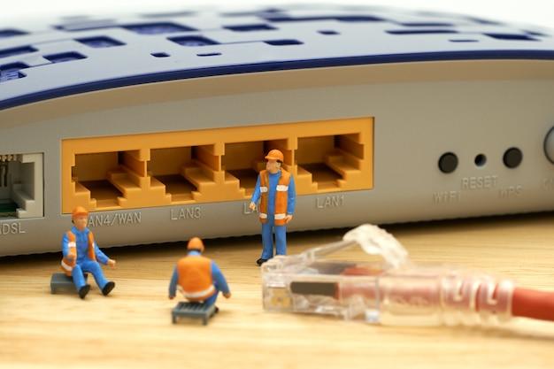 Pessoas em miniatura conexão de lan de trabalhador de construção ou conectar