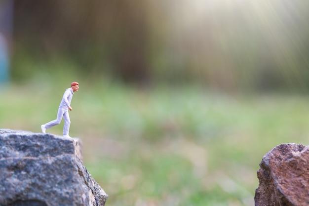 Pessoas em miniatura: correndo na falésia da rocha com fundo de natureza