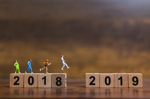 Pessoas em miniatura correndo no bloco de madeira número 2019