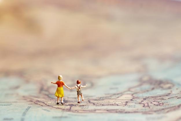 Pessoas em miniatura, crianças com irmão com globo andando para o destino