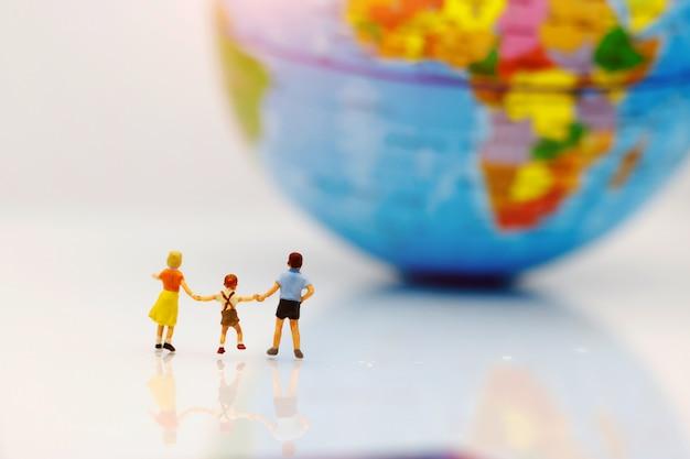 Pessoas em miniatura, crianças com irmão com globo caminhando para o destino