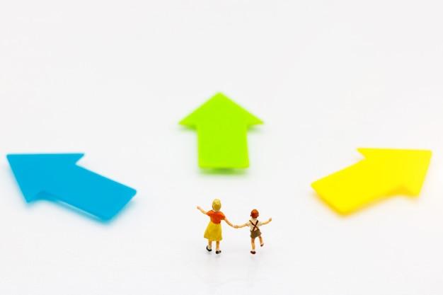 Pessoas em miniatura: crianças em pé com a escolha do caminho da seta. conceito de decisão.