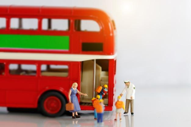 Pessoas em miniatura, crianças entrando no ônibus escolar com o professor.