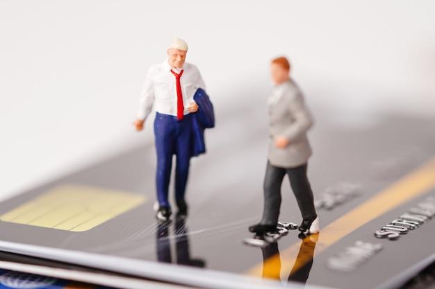 Pessoas em miniatura de homem de negócios ficam no cartão de crédito, conceito de finanças de negócios de gestão.