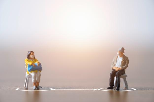 Pessoas em miniatura de homem e mulher usando máscara facial e sentam-se na cadeira, mantendo distância em público para evitar que o surto de vírus corona covid-19 espalhe infecção pandêmica.