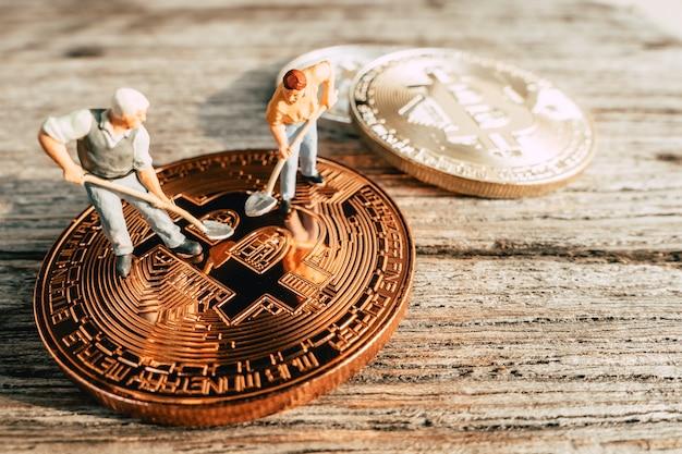 Pessoas em miniatura de mineração bitcoin cavando no valioso fundo madeira de moeda