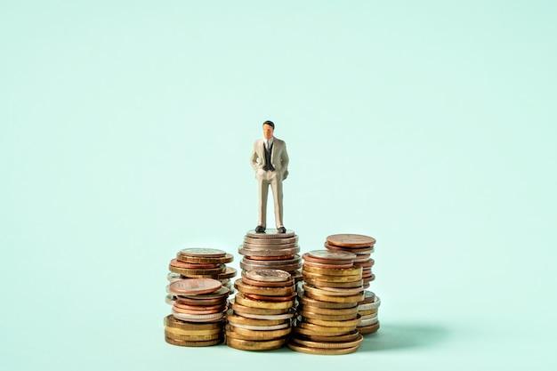 Pessoas em miniatura defendem o conceito de negócios e equipes de moedas