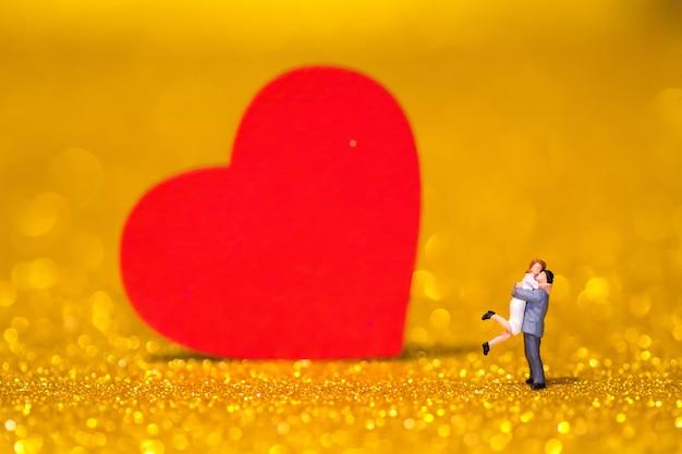 Pessoas em miniatura e coração vermelho. um casal apaixonado em um fundo radiante.