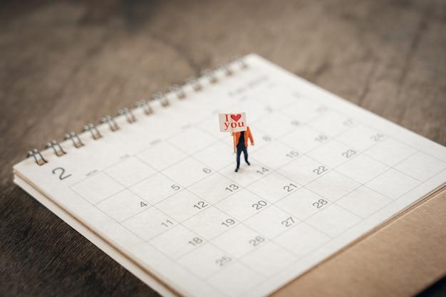 Pessoas em miniatura em pé no calendário. dia 14 encontra o dia dos namorados. coração vermelho