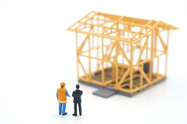 Pessoas em miniatura em pé verifique a qualidade da casa.