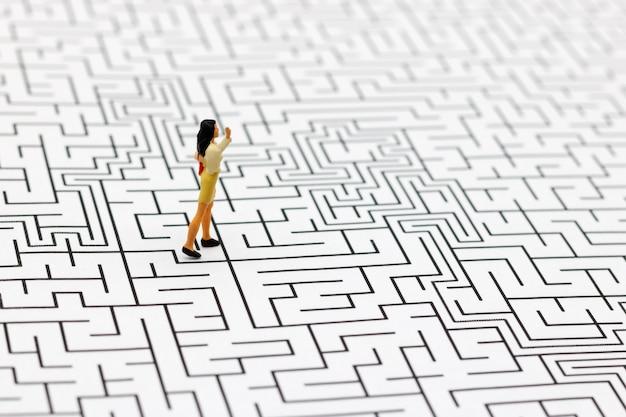 Pessoas em miniatura: empresária em pé no centro do labirinto.