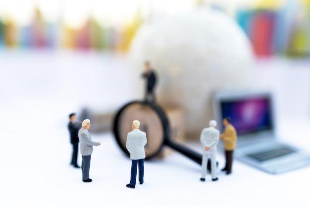 Pessoas em miniatura: empresário com globo branco e laptop, use uma lupa para obter o número um. recrutamento, encontrar o empregado e o conceito de negócio.