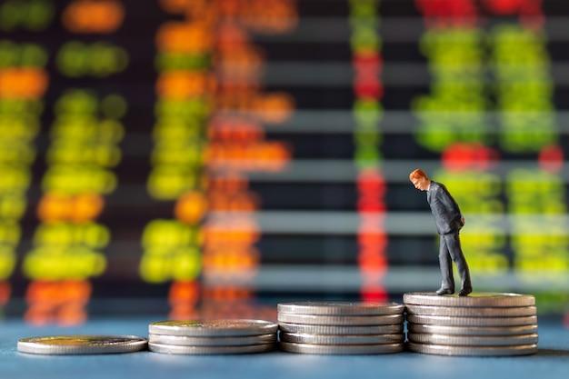 Pessoas em miniatura, empresário de pé na pilha de moedas com exibição de gráfico