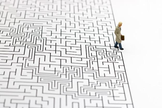 Pessoas em miniatura: empresário de pé no acabamento do labirinto. conceitos de encontrar uma solução, resolução de problemas e desafios.