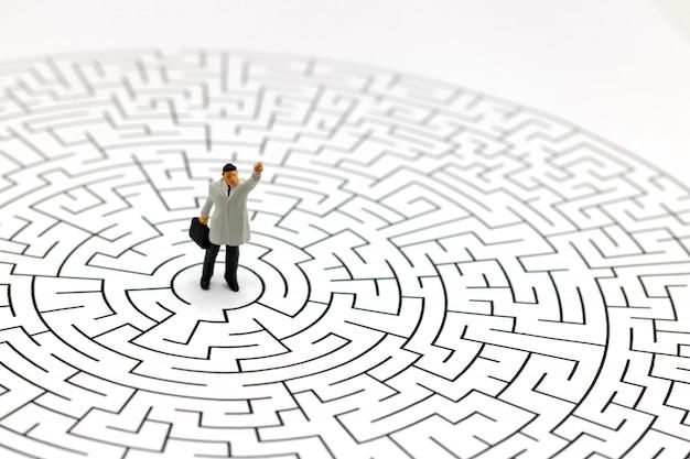 Pessoas em miniatura: empresário de pé no centro do labirinto.