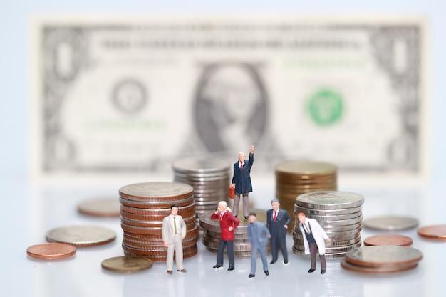 Pessoas em miniatura: empresário de pé no empilhamento de moedas