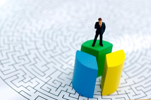 Pessoas em miniatura: empresário de pé no topo do bloco de madeira com labirinto.