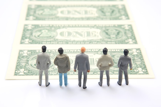 Pessoas em miniatura. empresário diferente fica perto do dinheiro do dólar. investimentos e ganhos para o trabalho