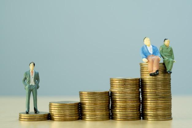 Pessoas em miniatura: empresário e velho casal figura sentada na pilha de moedas. poupança, seguro, conceito de planejamento de aposentadoria.