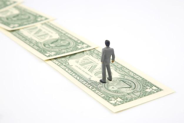 Pessoas em miniatura. empresário fica perto do dinheiro do dólar. investimentos e ganhos para o trabalho