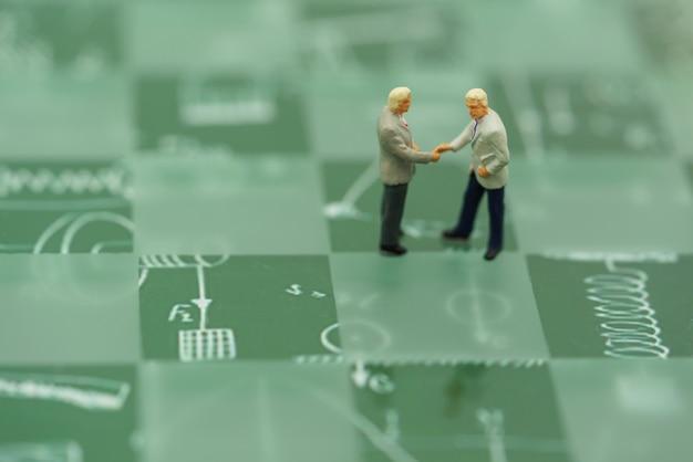 Pessoas em miniatura empresários aperto de mão com fundo verde.