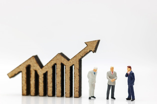Pessoas em miniatura: empresários de pé com gráfico, finanças, investimento e crescimento no conceito de negócio.