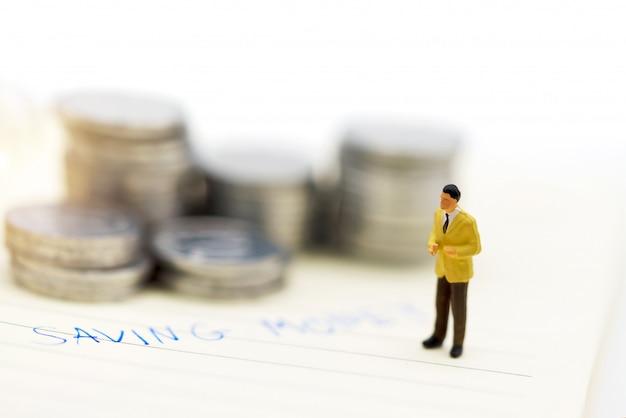 Pessoas em miniatura: empresários de pé com pilha de moedas, finanças e conceito de investimento.
