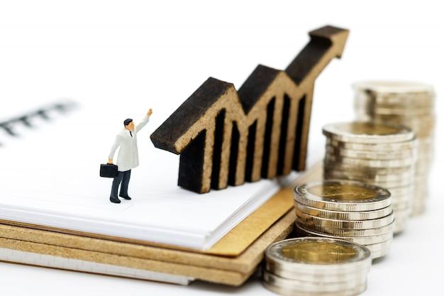 Pessoas em miniatura: empresários de pé na pilha de moedas com gráfico, finanças, investimento e crescimento no conceito de negócio.