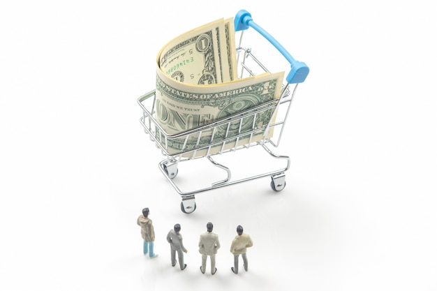Pessoas em miniatura. empresários ficam perto de uma cesta de supermercado com dólares. negócio de bens de consumo. conceito de indústria industrial